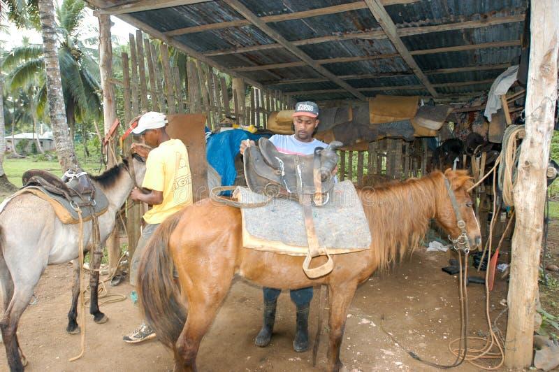 Άνθρωποι που προετοιμάζουν τα άλογα για το ταξίδι τουριστών στοκ εικόνα