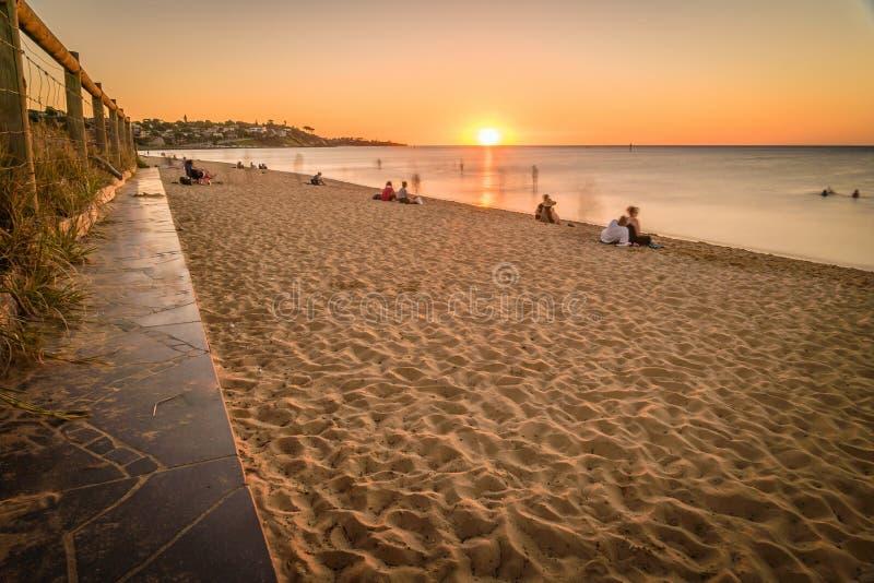 Άνθρωποι που προσέχουν το ηλιοβασίλεμα στην παραλία σε Frankston, Αυστραλία στοκ εικόνα