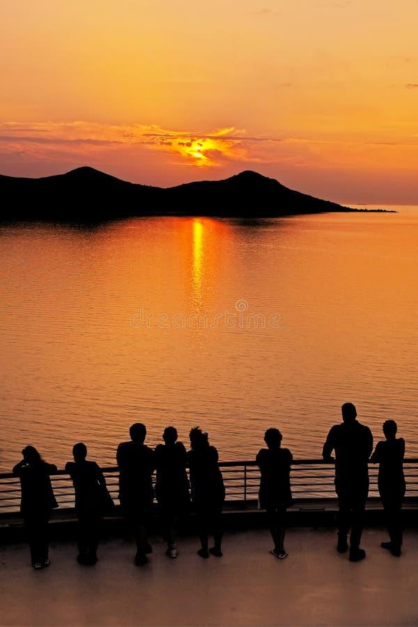 Άνθρωποι που προσέχουν το παράκτιο ηλιοβασίλεμα στοκ εικόνες