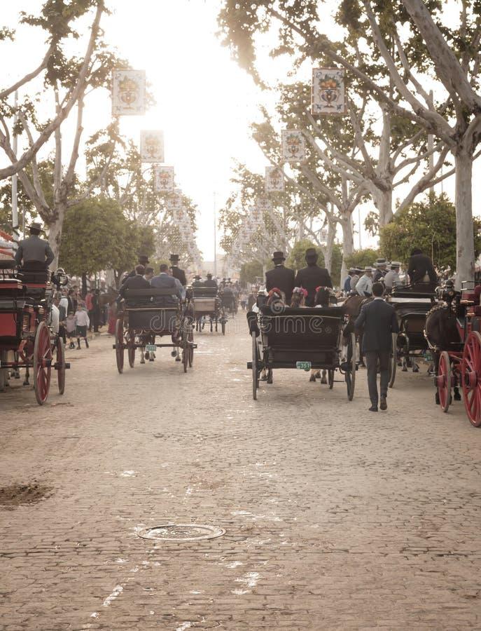 Άνθρωποι που ταξιδεύουν στις ένα συρμένες άλογο μεταφορές στην έκθεση της Σεβίλης στοκ φωτογραφίες