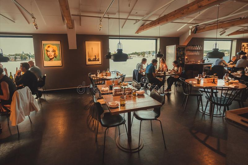 Άνθρωποι που τρώνε τα τρόφιμα στο εστιατόριο με την άποψη νερού, στο πολιτιστικό κέντρο Fotografiska στοκ εικόνα
