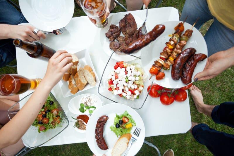 Άνθρωποι που τρώνε τα ψημένα στη σχάρα πιάτα στοκ φωτογραφία με δικαίωμα ελεύθερης χρήσης