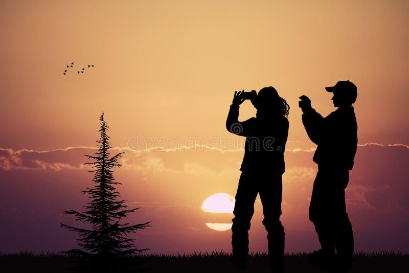 Άνθρωποι που φωτογραφίζουν το ηλιοβασίλεμα με το τηλέφωνο κυττάρων τους απεικόνιση αποθεμάτων