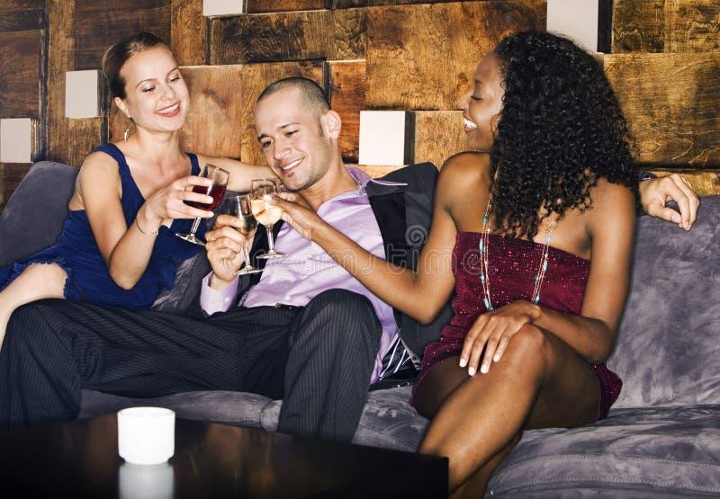 Άνθρωποι που ψήνουν τα ποτά στον καναπέ στο φραγμό στοκ εικόνες με δικαίωμα ελεύθερης χρήσης