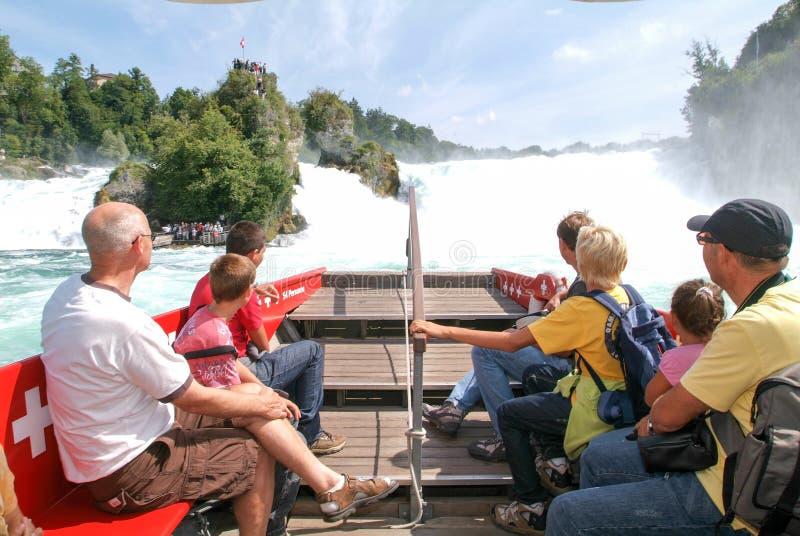 Άνθρωποι σε μια βάρκα τουριστών που πλησιάζει τους καταρράκτες του Ρήνου στοκ φωτογραφία