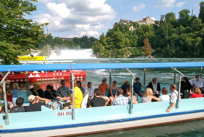 Άνθρωποι σε μια βάρκα τουριστών που πλησιάζει τους καταρράκτες του Ρήνου στοκ εικόνες