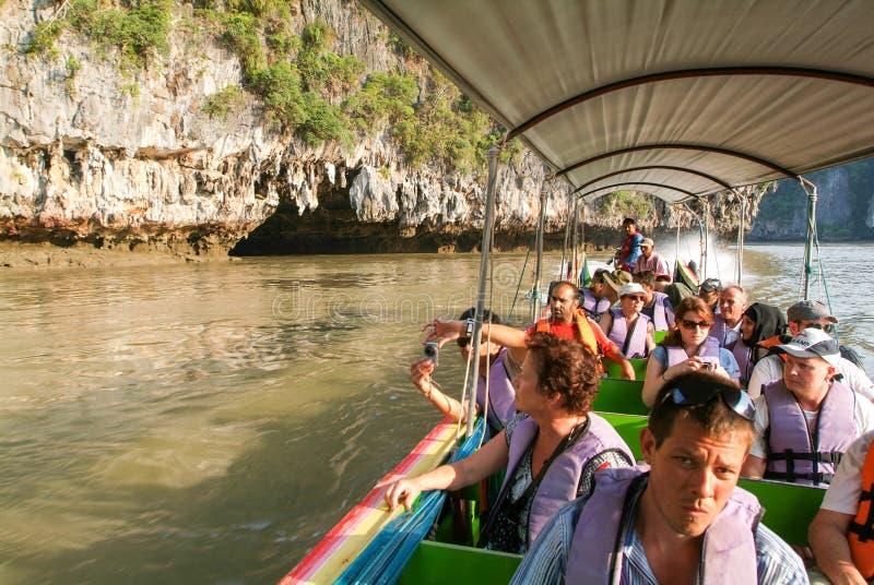 Άνθρωποι σε μια βάρκα τουριστών που τρέχει μέσω μιας σπηλιάς στοκ φωτογραφίες