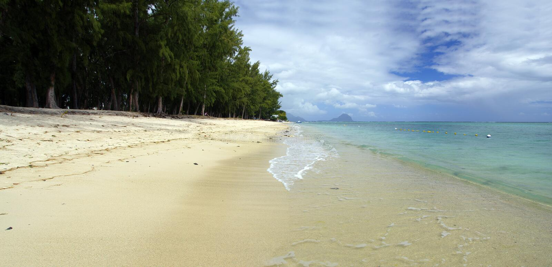 Άνθρωποι σε μια ηλιόλουστη μέρα περπατώντας στη δημόσια παραλία Flic en Flac με τροπικά δέντρα στην άκρη του Ινδικού Ωκεανού, Μαυ στοκ φωτογραφία