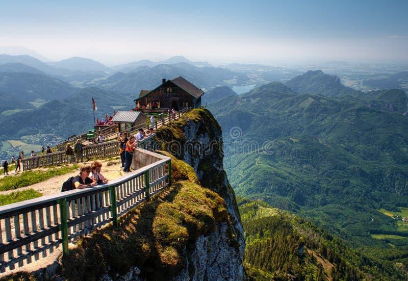 Άνθρωποι σε μια οπτική γωνία σε μια καλύβα βουνού στην κορυφή του βουνού Schafberg στοκ φωτογραφία