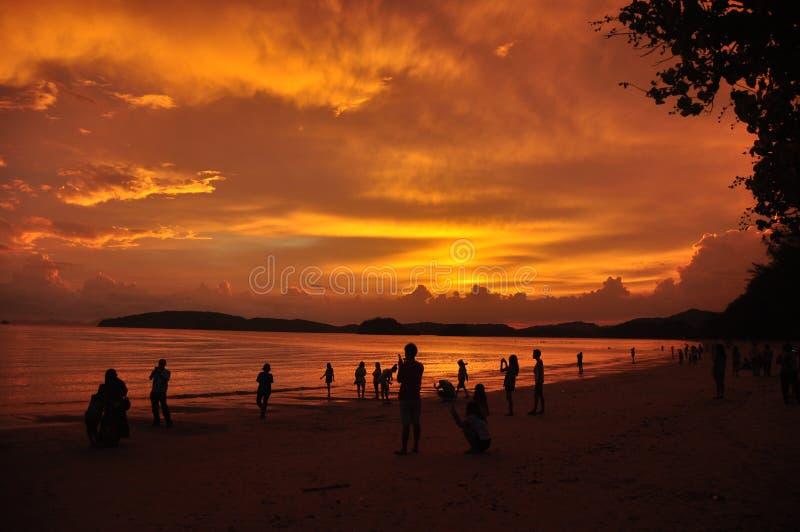 Άνθρωποι στην αμμώδη ακτή στο ηλιοβασίλεμα, σκιαγραφίες των ανθρώπων που ξοδεύουν το χρόνο στην τροπική ακτή με το χρυσό φωτεινό  στοκ εικόνες