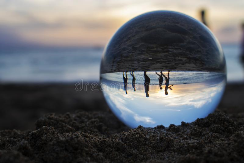 Άνθρωποι στον περίπατο σκιαγραφιών μέσα στην εικόνα σφαιρών γυαλιού του ηλιοβασιλέματος στο Β στοκ εικόνα με δικαίωμα ελεύθερης χρήσης