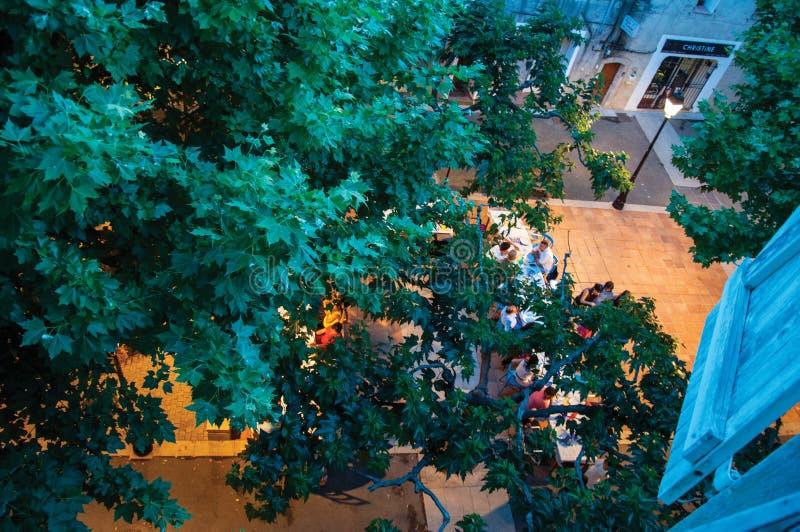 Άνθρωποι στο τετραγωνικό εστιατόριο με τους κλάδους του στις αρχές βραδιού σε Rians στοκ εικόνες