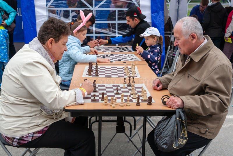 Άνθρωποι του διαφορετικού σκακιού παιχνιδιού ηλικιών και ελεγκτές στην οδό στοκ φωτογραφία