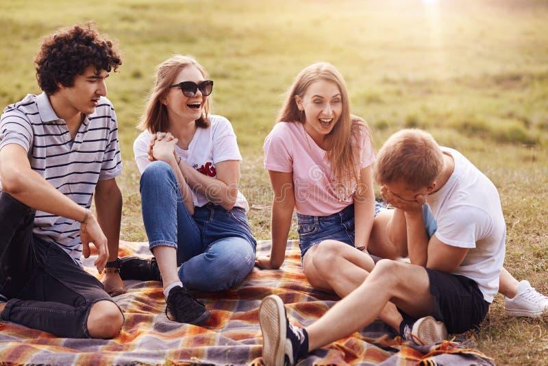 Άνθρωποι, φιλία και διασκέδαση Τέσσερις φίλοι ανδρών και γυναικών περνούν το Σαββατοκύριακο υπαίθριο, γελούν στις αστείες ιστορίε στοκ εικόνες