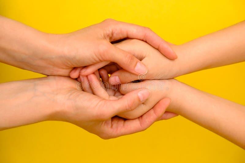 Άνθρωποι, φιλανθρωπία, οικογένεια και έννοια προσοχής - κλείστε επάνω των χεριών γυναικών κρατώντας τα χέρια κοριτσιών στοκ εικόνα με δικαίωμα ελεύθερης χρήσης