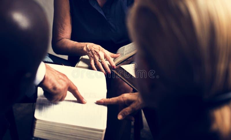 Άνθρωποι χριστιανισμού ομάδας που διαβάζουν τη Βίβλο από κοινού στοκ εικόνα