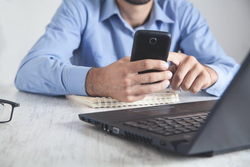Άνθρωπος που χρησιμοποιεί smartphone Εργασία στο γραφείο στοκ εικόνες με δικαίωμα ελεύθερης χρήσης