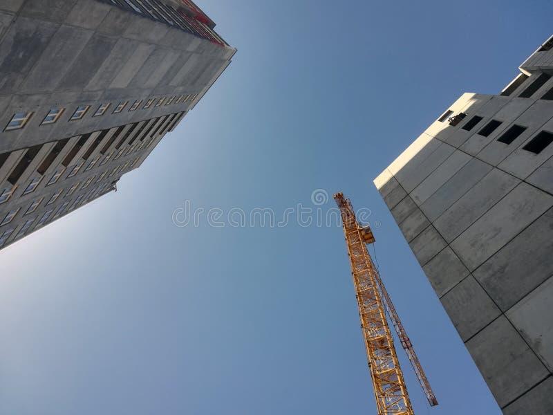 Άνοδοι γερανών οικοδόμησης επάνω από δύο κτήρια Κατώτατο σημείο επάνω στην άποψη σχετικά με το υπόβαθρο μπλε ουρανού στοκ φωτογραφία με δικαίωμα ελεύθερης χρήσης