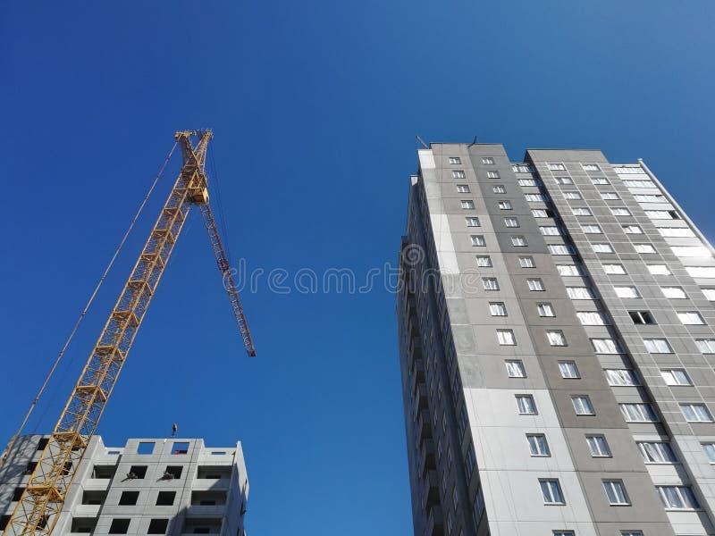 Άνοδοι γερανών οικοδόμησης επάνω από δύο κτήρια Κατώτατο σημείο επάνω στην άποψη σχετικά με το υπόβαθρο μπλε ουρανού στοκ εικόνα με δικαίωμα ελεύθερης χρήσης