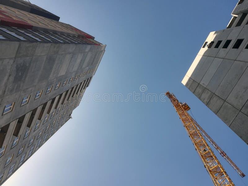 Άνοδοι γερανών οικοδόμησης επάνω από δύο κτήρια Κατώτατο σημείο επάνω στην άποψη σχετικά με το υπόβαθρο μπλε ουρανού στοκ φωτογραφία