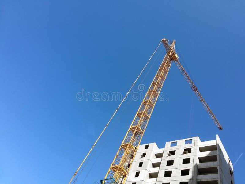 Άνοδοι γερανών οικοδόμησης επάνω από το κτήριο Κατώτατο σημείο επάνω στην άποψη σχετικά με το υπόβαθρο μπλε ουρανού στοκ φωτογραφίες με δικαίωμα ελεύθερης χρήσης