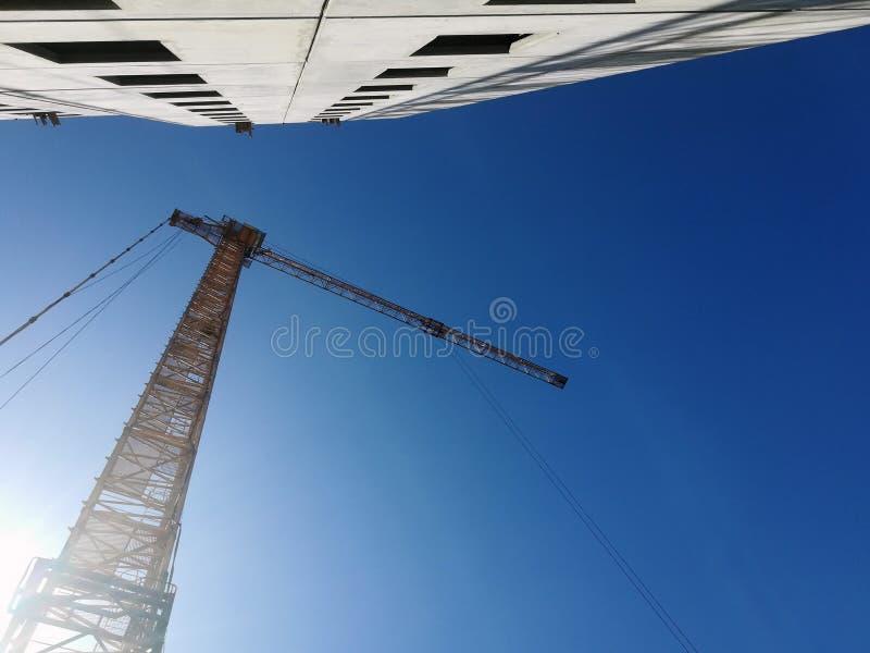 Άνοδοι γερανών οικοδόμησης επάνω από το κτήριο Κατώτατο σημείο επάνω στην άποψη σχετικά με το υπόβαθρο μπλε ουρανού στοκ εικόνες με δικαίωμα ελεύθερης χρήσης