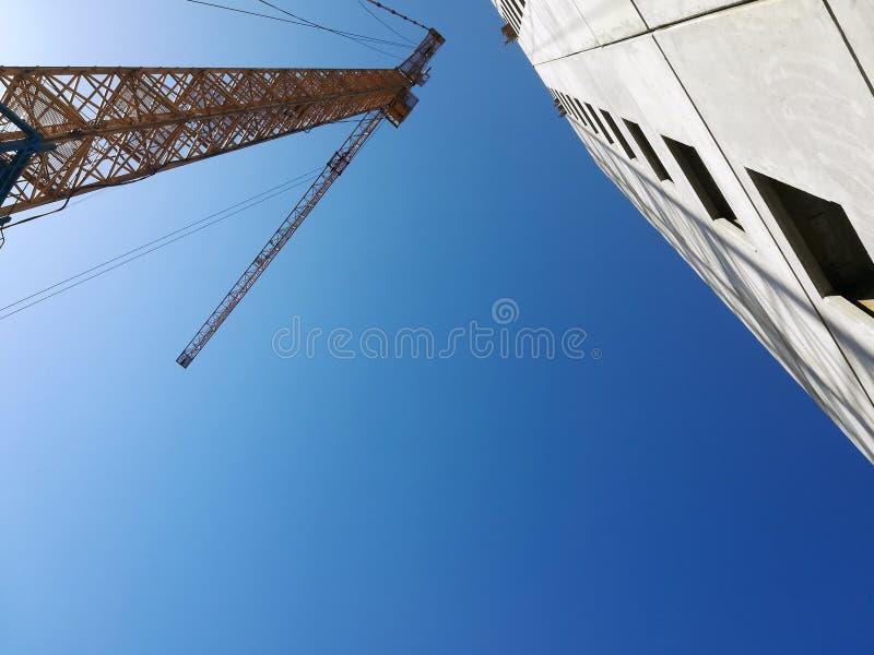 Άνοδοι γερανών οικοδόμησης επάνω από το κτήριο Κατώτατο σημείο επάνω στην άποψη σχετικά με το υπόβαθρο μπλε ουρανού στοκ φωτογραφία με δικαίωμα ελεύθερης χρήσης