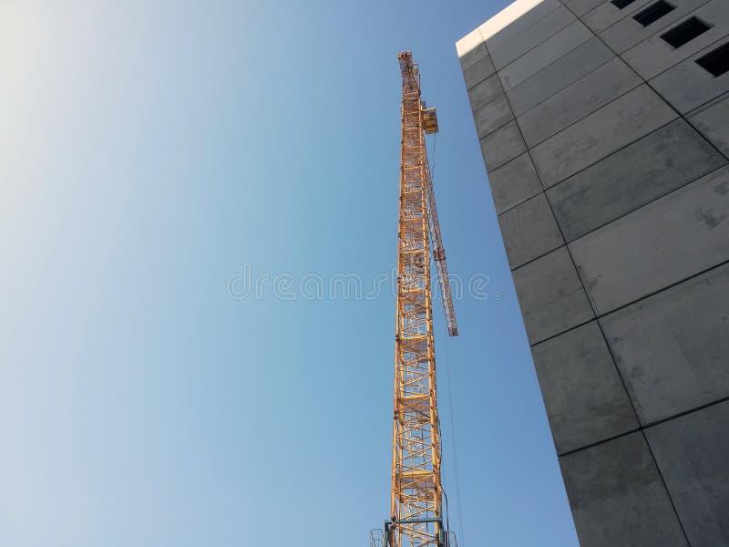 Άνοδοι γερανών οικοδόμησης επάνω από το κτήριο Κατώτατο σημείο επάνω στην άποψη σχετικά με το υπόβαθρο μπλε ουρανού στοκ εικόνες