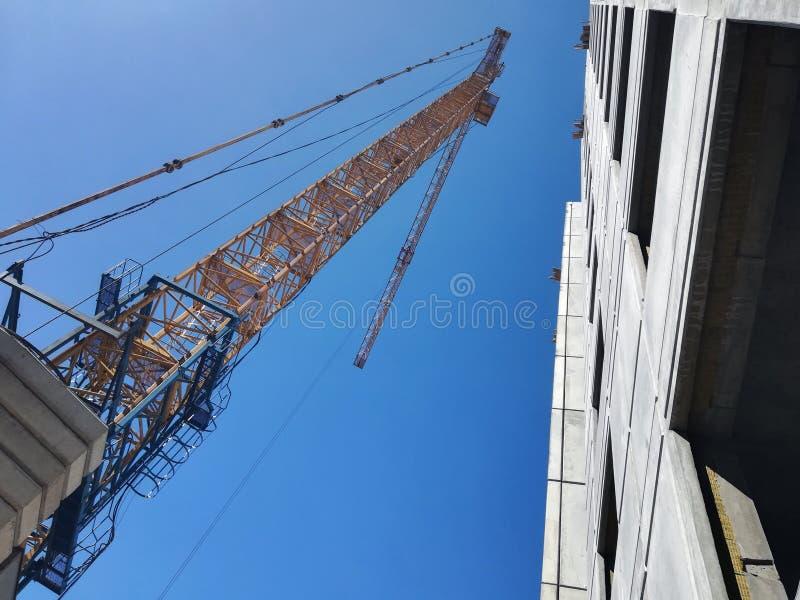 Άνοδοι γερανών οικοδόμησης επάνω από το κτήριο Κατώτατο σημείο επάνω στην άποψη σχετικά με το υπόβαθρο μπλε ουρανού στοκ εικόνα με δικαίωμα ελεύθερης χρήσης
