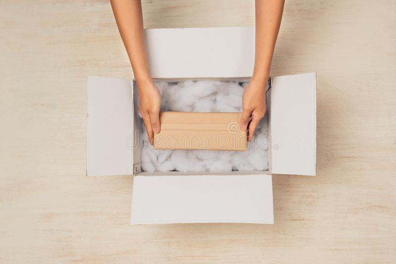 Άνοιγμα ενός κιβωτίου χαρτοκιβωτίων Χέρια που κρατούν το κιβώτιο δώρων στο κουτί από χαρτόνι στοκ φωτογραφία