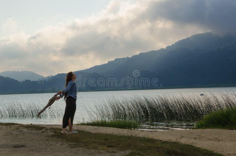 Άνοιξε τις αγκάλες του στην ακτή λιμνών, γύρισε το πρόσωπό του στον αέρα, στοκ εικόνες με δικαίωμα ελεύθερης χρήσης