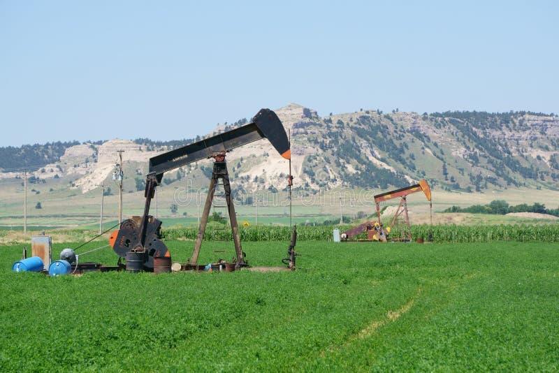 Άντληση πετρελαιοπηγών σε έναν αγροτικό τομέα της Νεμπράσκας στοκ φωτογραφίες