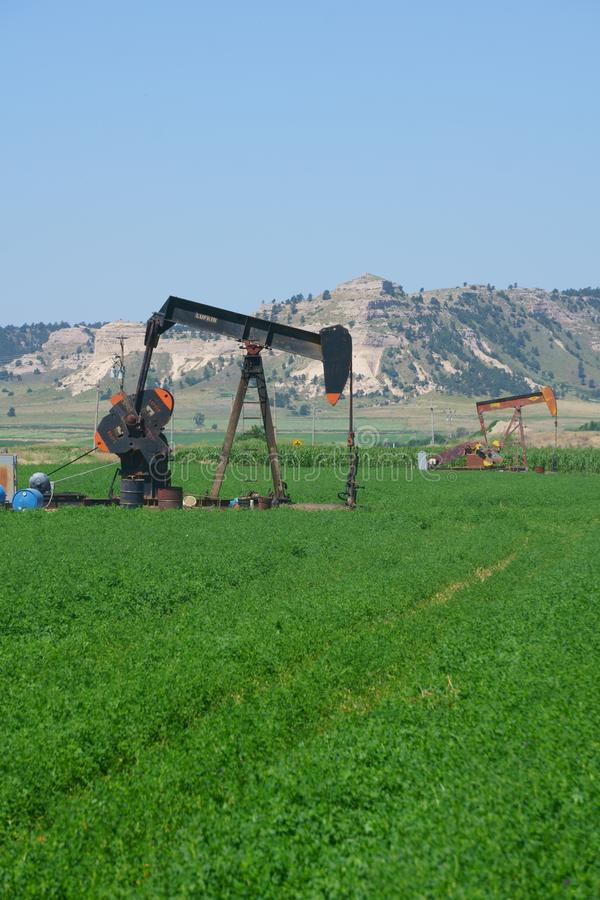 Άντληση πετρελαιοπηγών σε έναν αγροτικό τομέα της Νεμπράσκας στοκ εικόνες