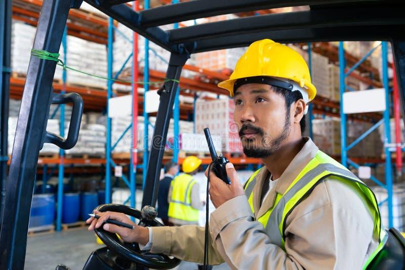 Άντρας εργαζόμενος μιλάει με γουόκι-τόκι ενώ οδηγεί περονοφόρα στην απ στοκ φωτογραφίες