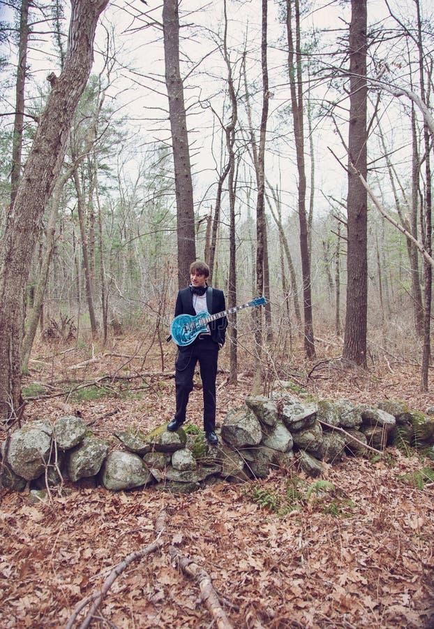Άντρας με κιθάρα στο δάσος στοκ φωτογραφία με δικαίωμα ελεύθερης χρήσης