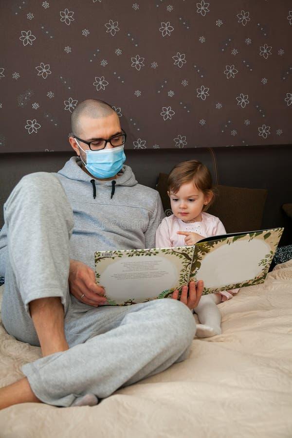 Άντρας με προστατευτική μάσκα διαβάζει βιβλίο στην κόρη του στοκ φωτογραφία με δικαίωμα ελεύθερης χρήσης