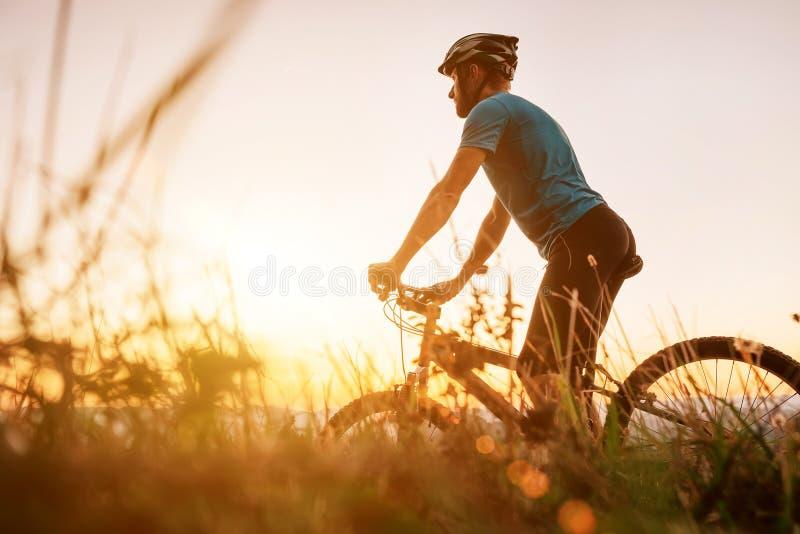 Άντρας μοτοσικλετιστής συναντά ένα ηλιοβασίλεμα στην κορυφή του λόφου πάνω από την πόλη Εικόνα έννοιας ενεργών αθλητών στοκ εικόνες