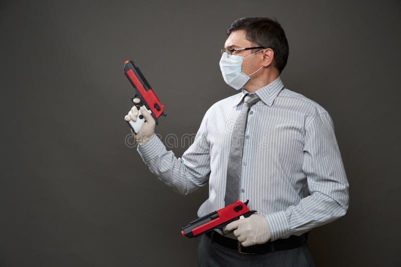 Άντρας ντυμένος επιχειρηματίας, ποζάρει στο στούντιο σε γκρίζο φόντο, μάσκα ιατρικού προσώπου και προστατευτικά γάντια, όπλο, γυα στοκ εικόνα