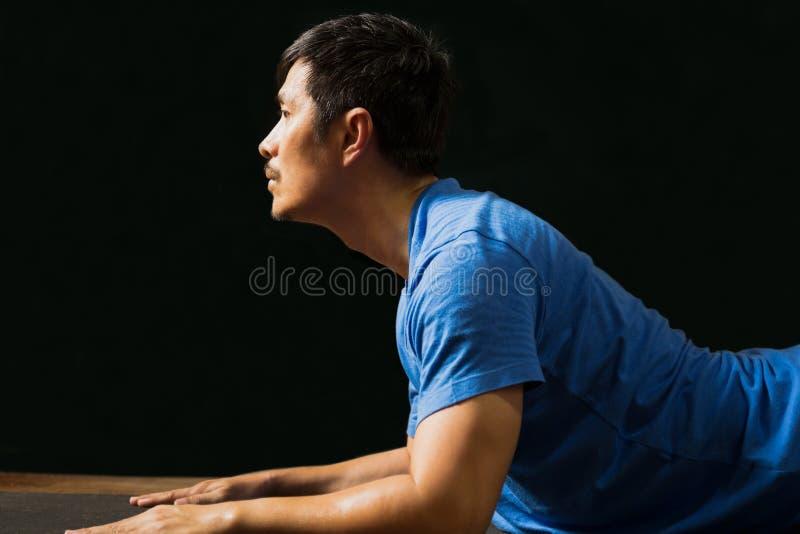 Άντρας που κάνει γυμναστική γιόγκα στο σπίτι κοινωνικός αποστάτης κορονοϊός στοκ εικόνα