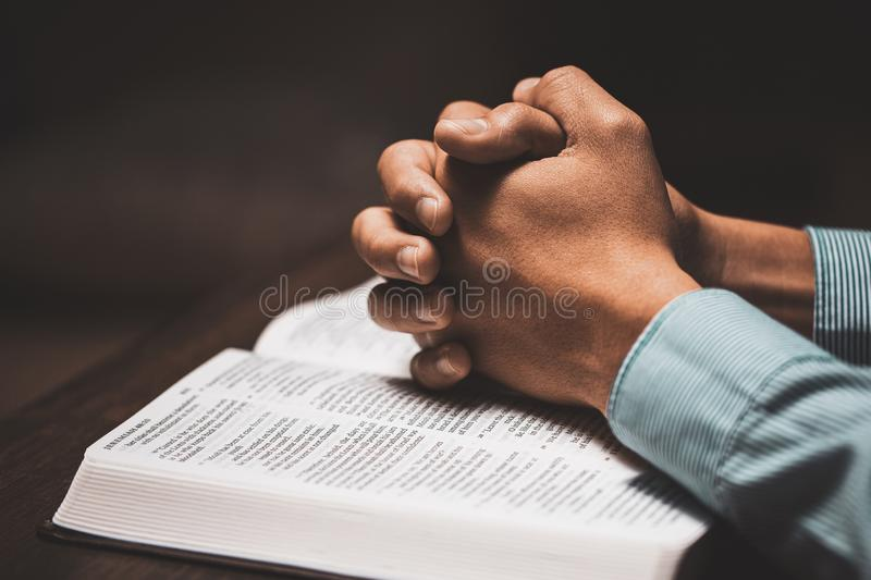 Άντρας που προσεύχεται με τα χέρια του σε μια Βίβλο στοκ εικόνα με δικαίωμα ελεύθερης χρήσης
