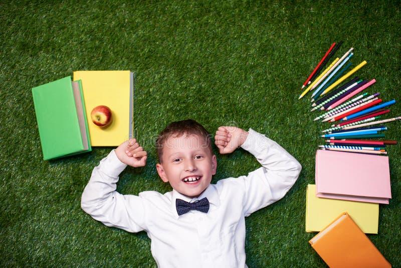 Άνωθεν ένα αγόρι με τα σημειωματάρια βρίσκεται στη χλόη και χαμογελά ο σπουδαστής εναπόκειται στα βιβλία και τα μολύβια στο χορτο στοκ εικόνες
