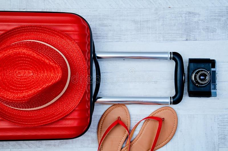 Άνωθεν κόκκινη βαλίτσα εκτός από τις σαγιονάρες και αναδρομική κάμερα στο ελαφρύ υπόβαθρο Ταξιδιού ή γυναίκα blogger ή θερινές δι στοκ εικόνες