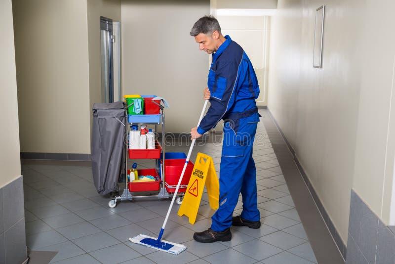 Άνδρας εργαζόμενος με τον καθαρίζοντας διάδρομο σκουπών στοκ φωτογραφίες με δικαίωμα ελεύθερης χρήσης