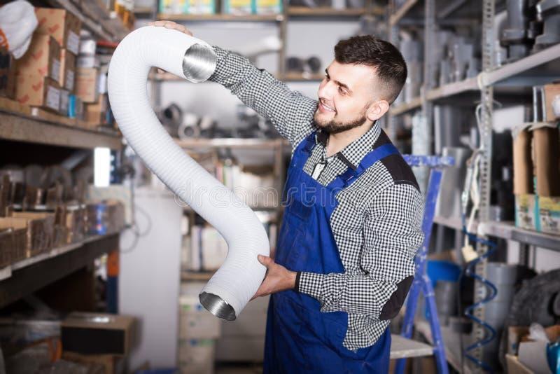 Άνδρας εργαζόμενος που επιλέγει το αργίλιο που κατασκευάζει τους σωλήνες στοκ εικόνες