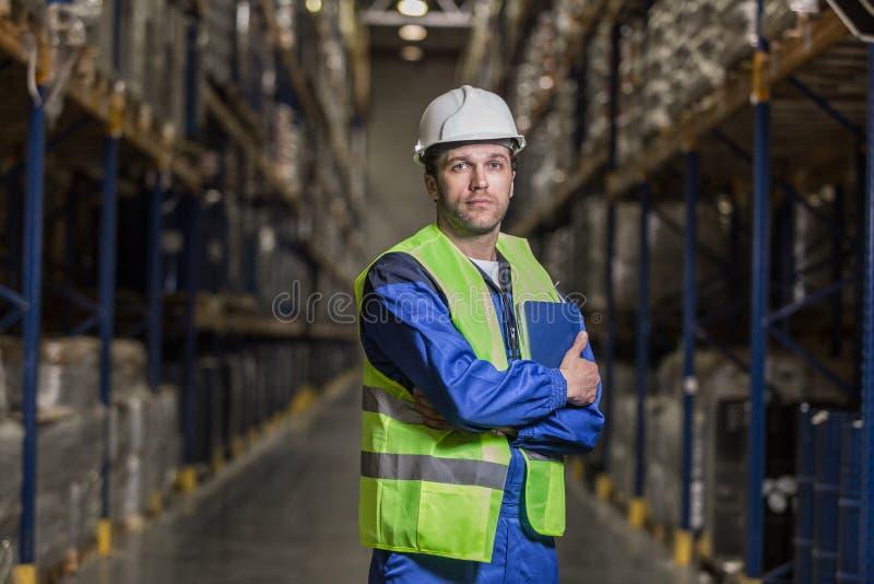 Άνδρας εργαζόμενος που στέκεται μεταξύ των selves με το σημειωματάριο στοκ εικόνες