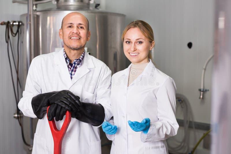 Άνδρας και γυναίκα μεταξύ του εξοπλισμού ζυθοποιείων στοκ εικόνα με δικαίωμα ελεύθερης χρήσης