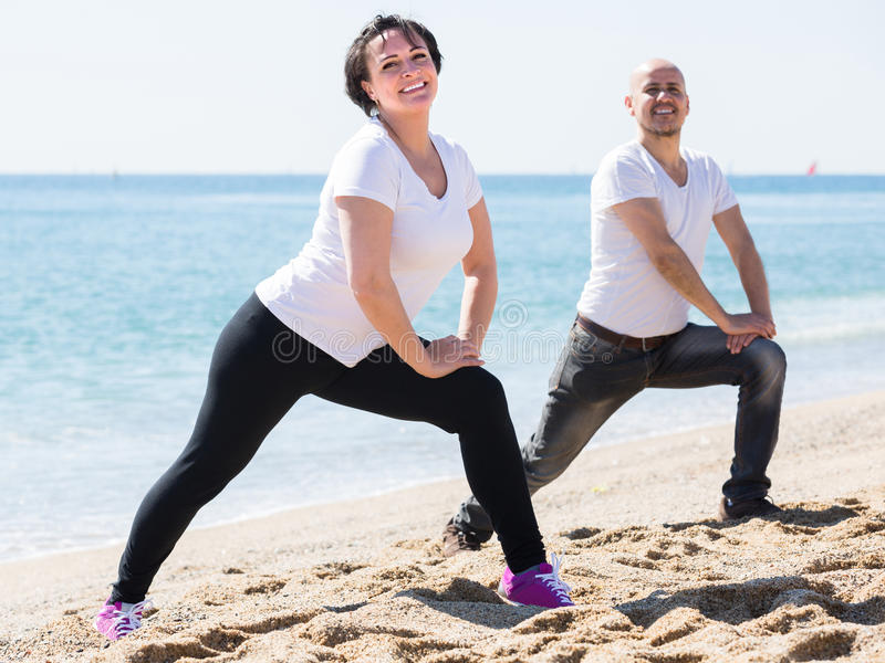 Άνδρας και γυναίκα που ασκούν μαζί στην παραλία στοκ φωτογραφία