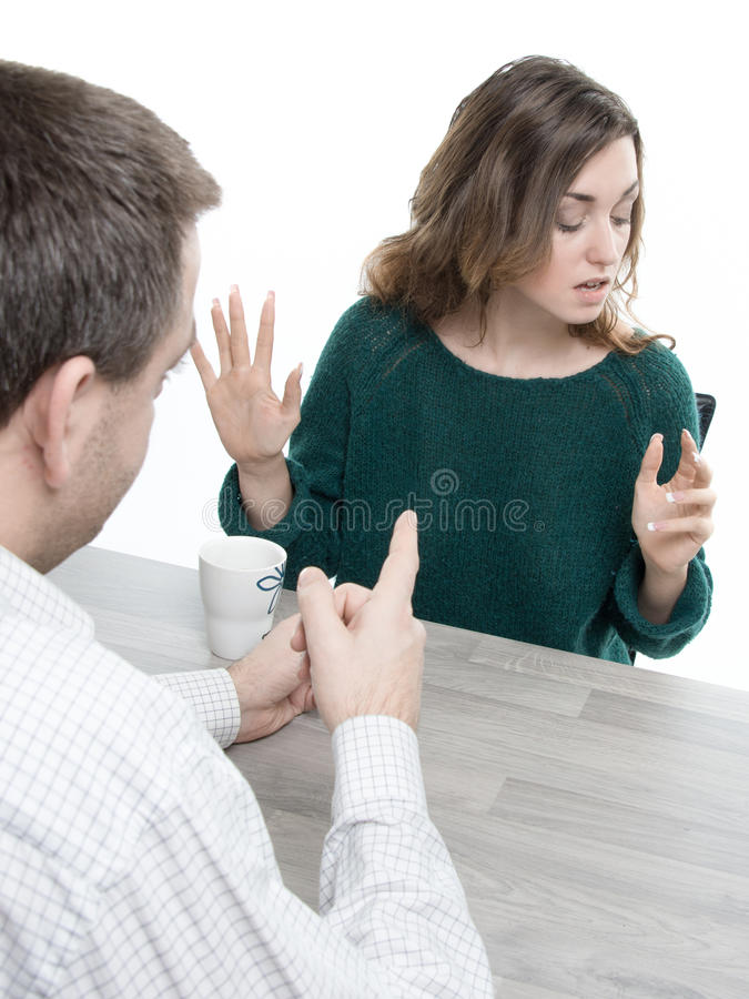 Άνδρας και γυναίκα που συζητούν σε έναν πίνακα, άνδρας που δείχνει και απόρριψη γυναικών στοκ φωτογραφία
