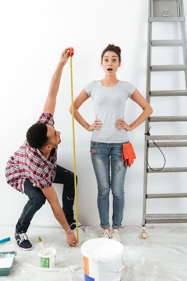 Άνδρας και γυναίκα που χρησιμοποιούν την ταινία μέτρου στοκ φωτογραφία