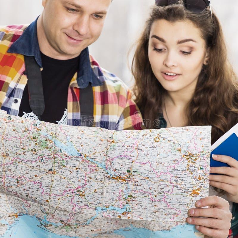 Άνδρας και μια γυναίκα που κρατά ένα διαβατήριο Εξετάστε το χάρτη, κατεύθυνση της μελέτης Ευρωπαίοι Μαζευμένος σε μια οργανωμένη  στοκ φωτογραφίες